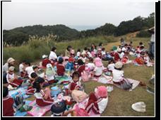 10月:若草山遠足 年中年長さんが若草山でお弁当を食べています。鹿に気をつけてね